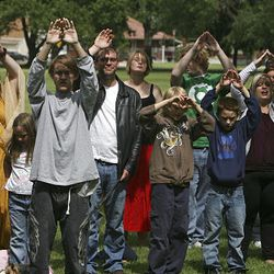 """A group participates in the opening ritual adoration of Rah during the second annual Pagan Pride Day, """"A Bridge to Understanding,"""" at Monroe Park in Ogden."""