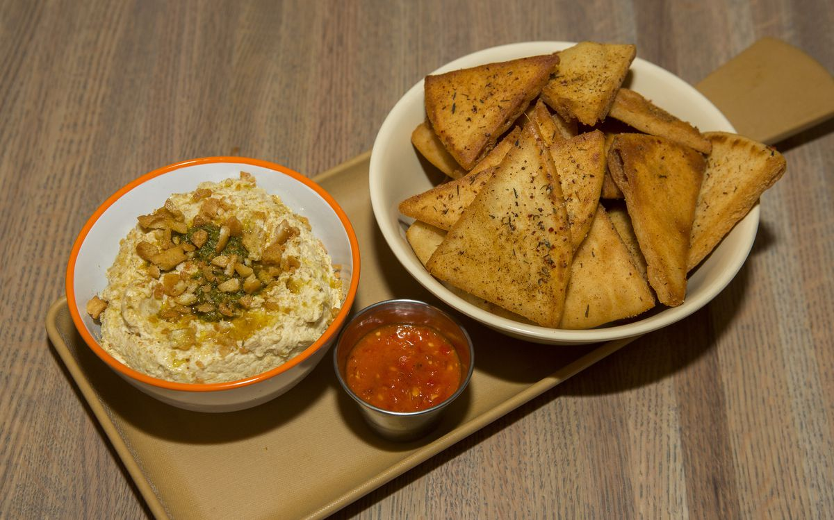 A bowl of hummus, red pepper dip, and a bowl of pita chips.