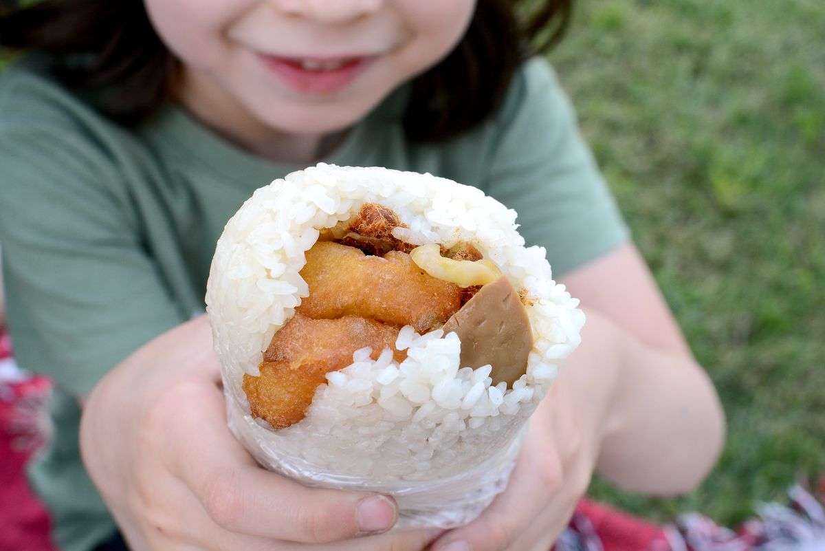 A rice roll filled with a doughnut, egg, and pickled mustard greens.