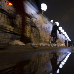 Balloons of the art project 'Lichtgrenze 2014' (lit. 'lightborder 2014') reflect in a puddle next to remains of the Berlin Wall at East Side Gallery in Berlin, Germany, Friday, Nov. 7, 2014. The light installation featuring 8,000 luminous white balloons commemorates the division of Berlin where the 25th anniversary of the fall of the wall is marked with numerous events on the weekend.