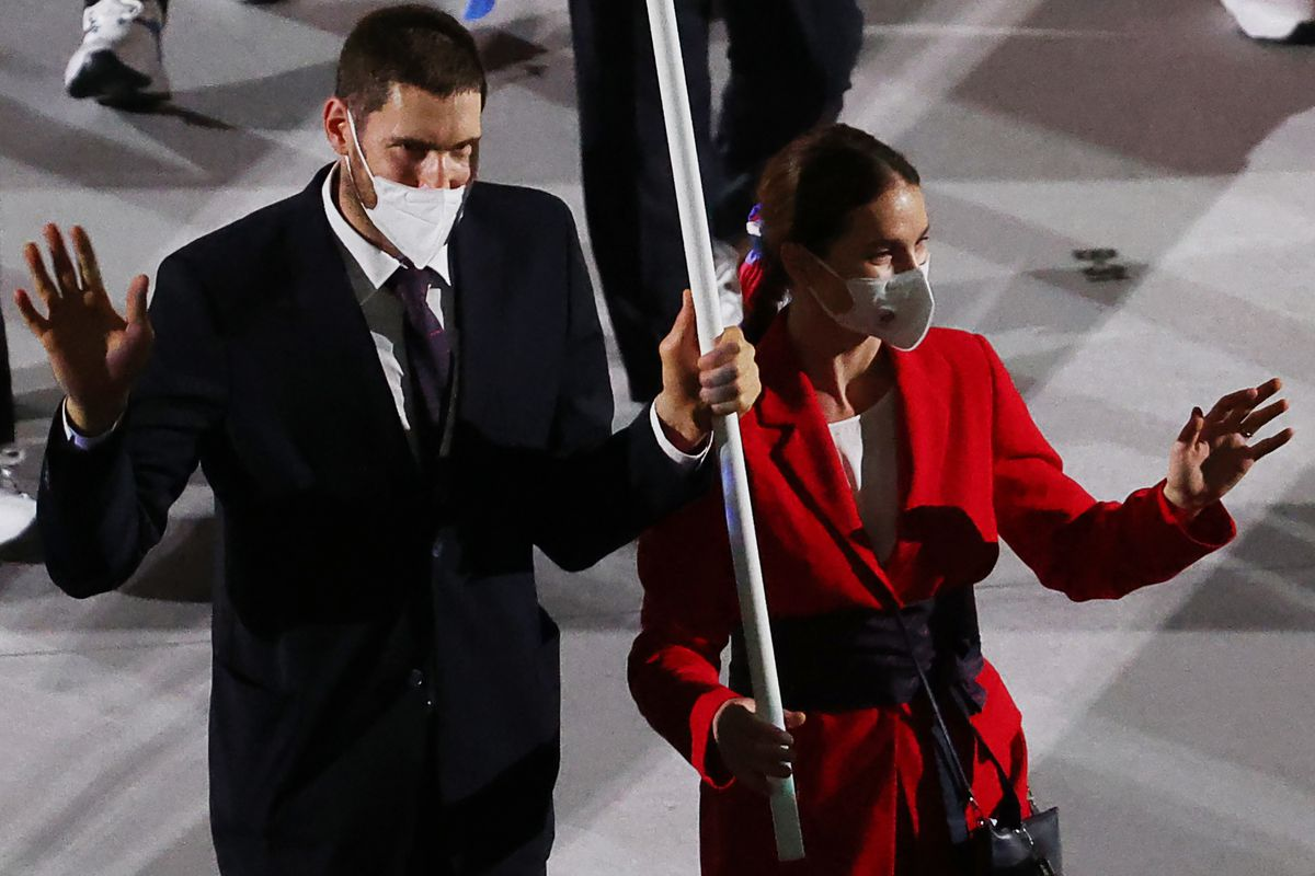 Fencer Sofya Velikaya and volleyball player Maxim Mikhailov of the ROC Team carry a ROC flag during the Parade of Nations at the opening ceremony of the Tokyo 2020 Summer Olympic Games at the National Stadium. Tokyo was to host the 2020 Summer Olympics from 24 July to 9 August 2020, however because of the COVID-19 pandemic the games have been postponed for a year and are due to take place from 23 July to 8 August 2021.