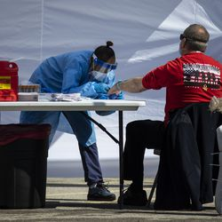 A Norwood Park Fire Department firefighter gets his blood drawn for a coronavirus antibody test by a Simple Laboratories phlebotomist at their drive-thru testing site in the parking lot of St. Rosalie Catholic Parish in Harwood Heights, Friday, May 1, 2020.