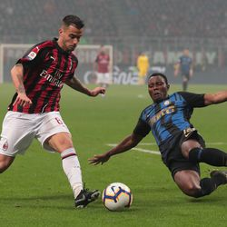 Fernandez Suso of AC Milan is challenged by Kwadwo Asamoah of FC Internazionale during the Serie A match between AC Milan and FC Internazionale at Stadio Giuseppe Meazza on March 17, 2019 in Milan, Italy.