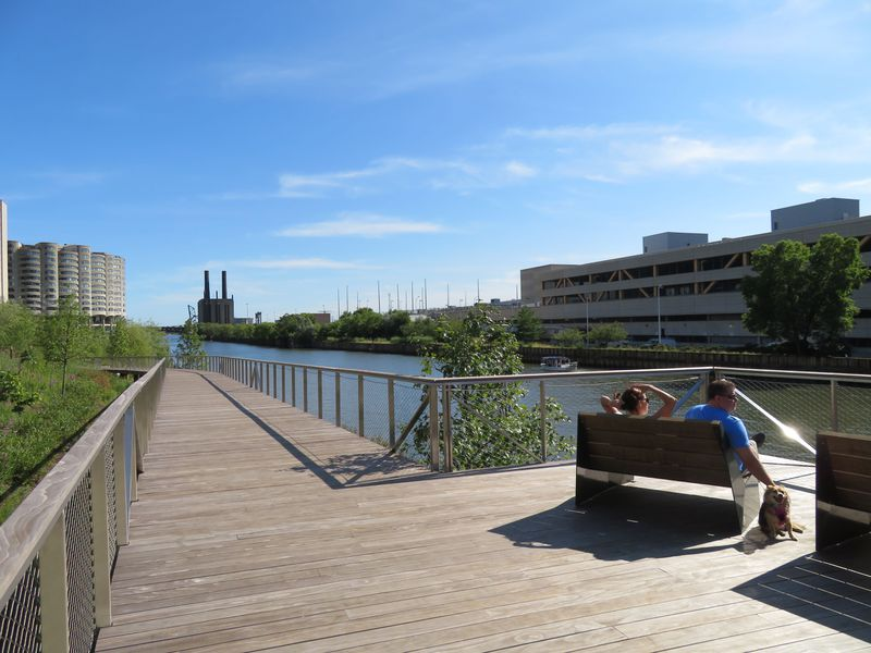 An elevated pathway gently slopes down to the river and curves to the left. A man and a woman sit on a wood bench facing the water next to a furry dog.