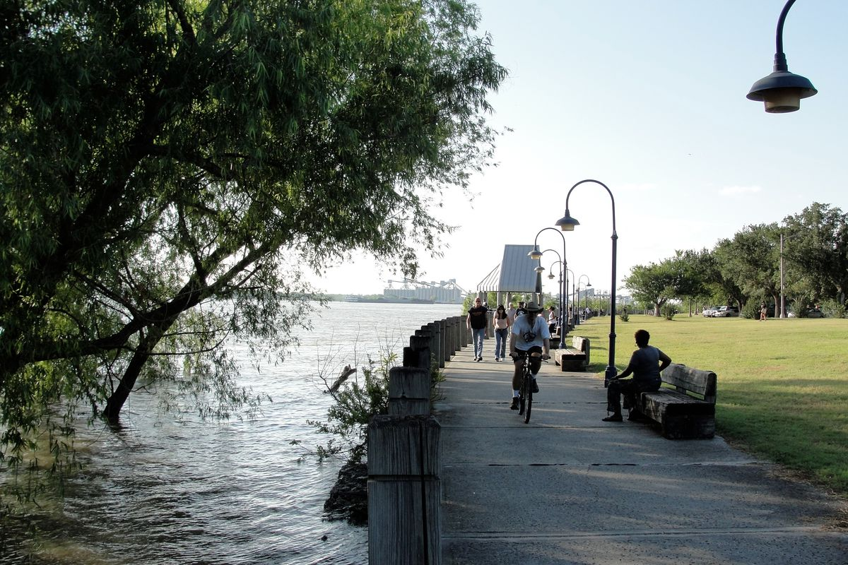 A concrete path hugs a grassy levee right next to a high river with trees growing in the water. Pedestrians, cyclists and distant buildings are visible.