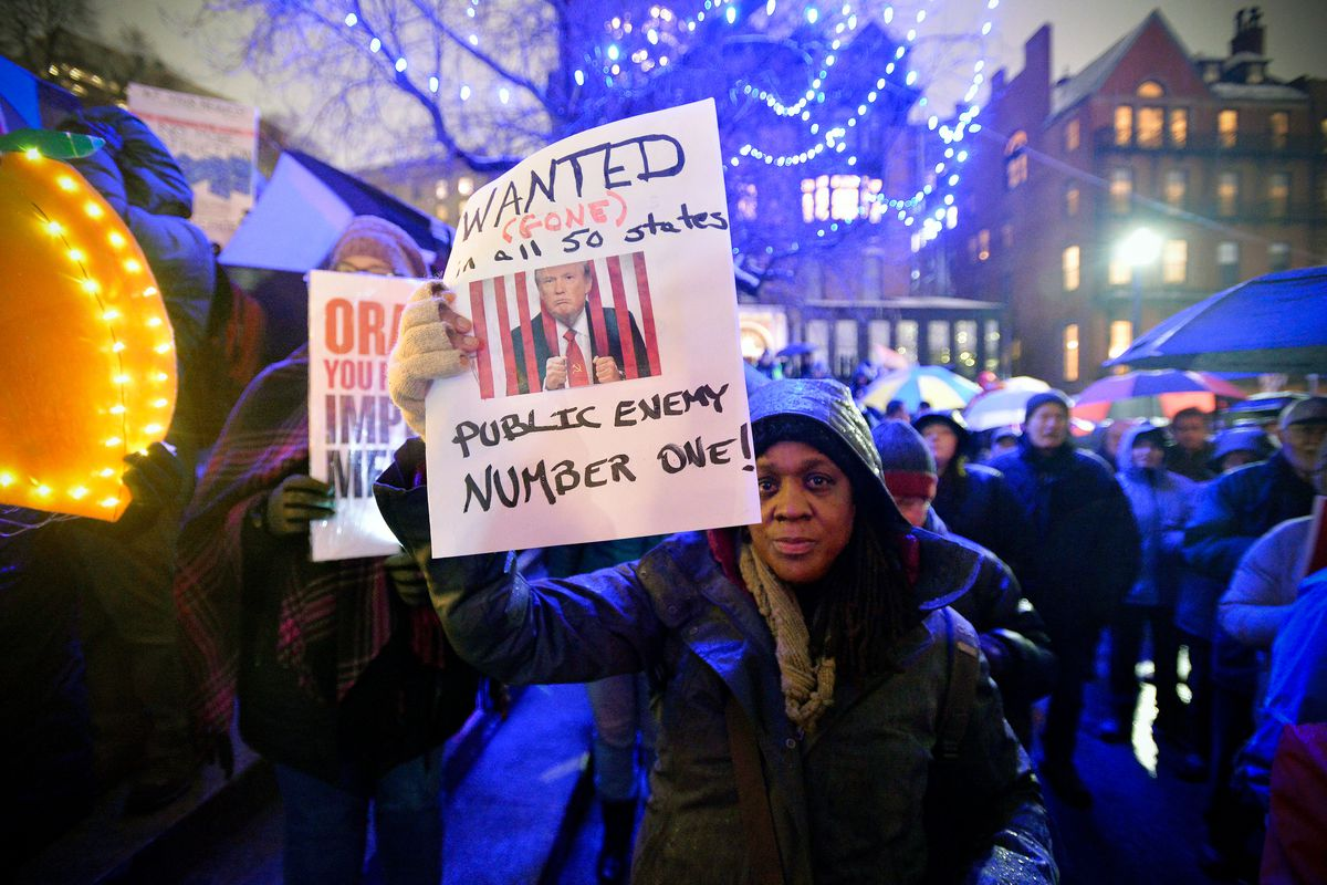 Protesters gathered on Boston Common during a rally where over a thousand people gathered in the rain and snow calling for the impeachment of President Donald Trump.