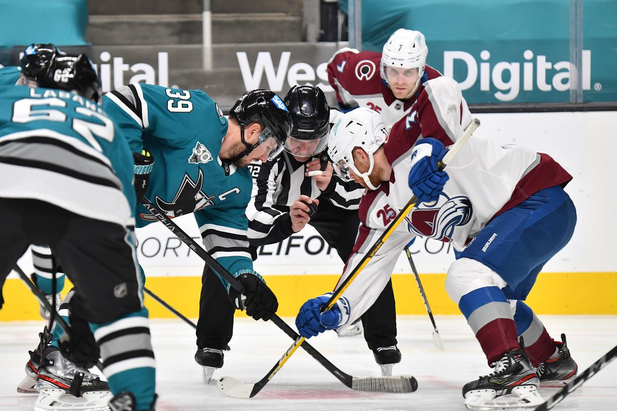 Logan Couture #39 of the San Jose Sharks takes a face-off against J.T. Compher #37 of the Colorado Avalanche at SAP Center on March 1, 2021 in San Jose, California.