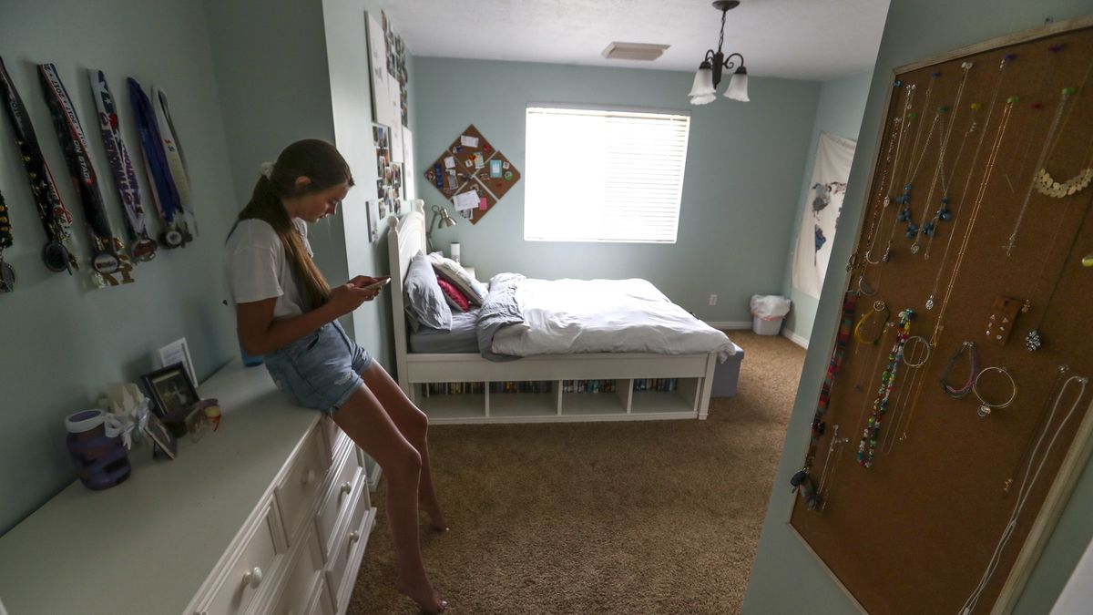 Katherine, who has struggled with overwhelming anxiety, connects with friends on her phone in her bedroom on Friday, July 27, 2018.