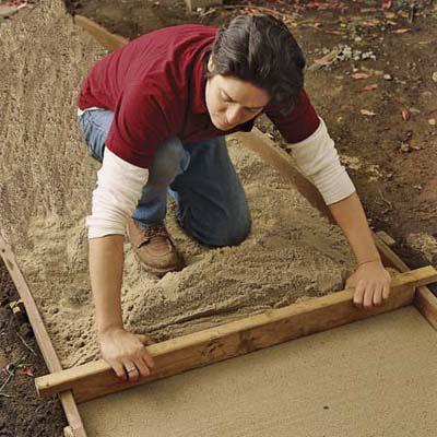 Man Grades Path With Sand To Make Brick Path