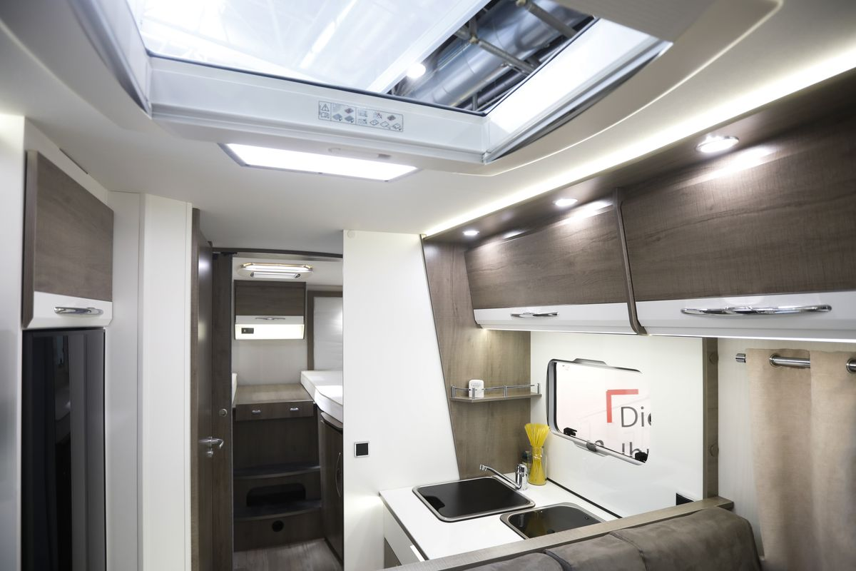 The center of the motorhome has brown upper storage cabinets, a galley kitchen, and a bathroom on the left.