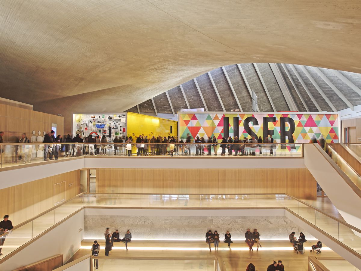 The interior of the Design Museum in London. There is a high curved ceiling, multiple levels, and a skylight.