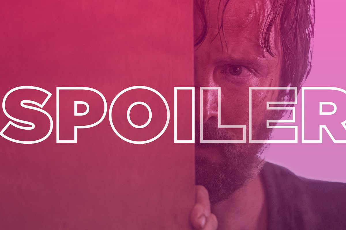 Jesse (Aaron Paul) peers out from behind a door.