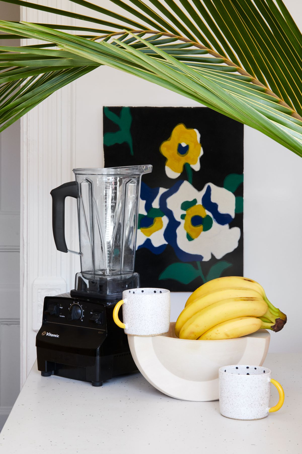 A set of kitchen items including a blender, bowl of fruit, and mugs on a kitchen counter.