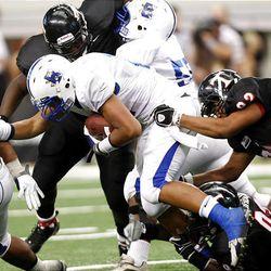 Bingham running back Harvey Langi dives into the line as the Miners play Euless (Texas) Trinity Monday in the Kirk Herbstreit Varsity Football Series at Dallas Cowboys Stadium in Arlington, Texas. Trinity won 42-21.