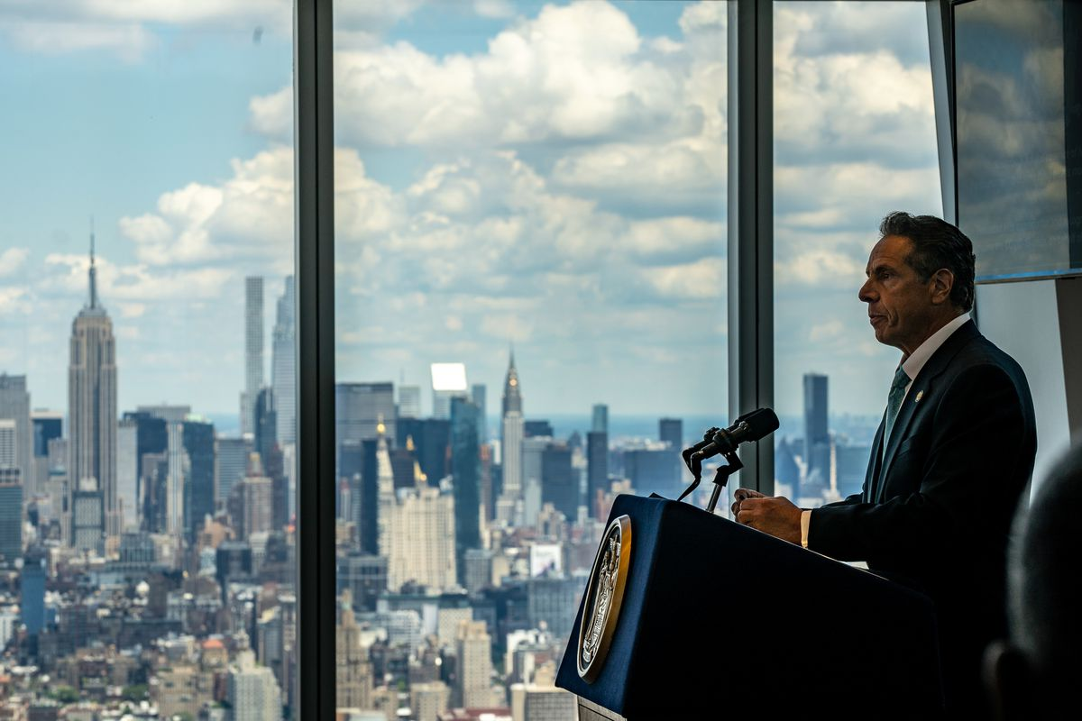 New York Governor Andrew Cuomo speaks at a podium indoors, with the New York City skyline visible behind the windows to his right.