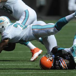 Sep 8, 2013; Cleveland, OH, USA; Cleveland Browns middle linebacker D'Qwell Jackson (52) upends Miami Dolphins running back Daniel Thomas (33) during the second quarter at FirstEnergy Stadium.