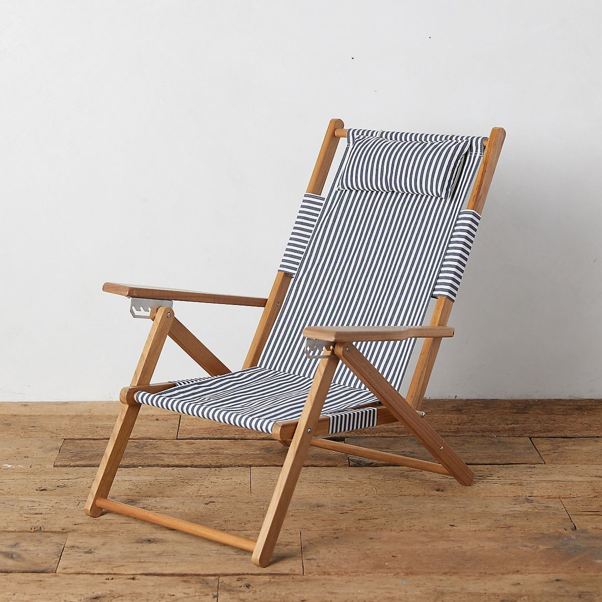 Folding wooden lounge chair with striped fabric seating.