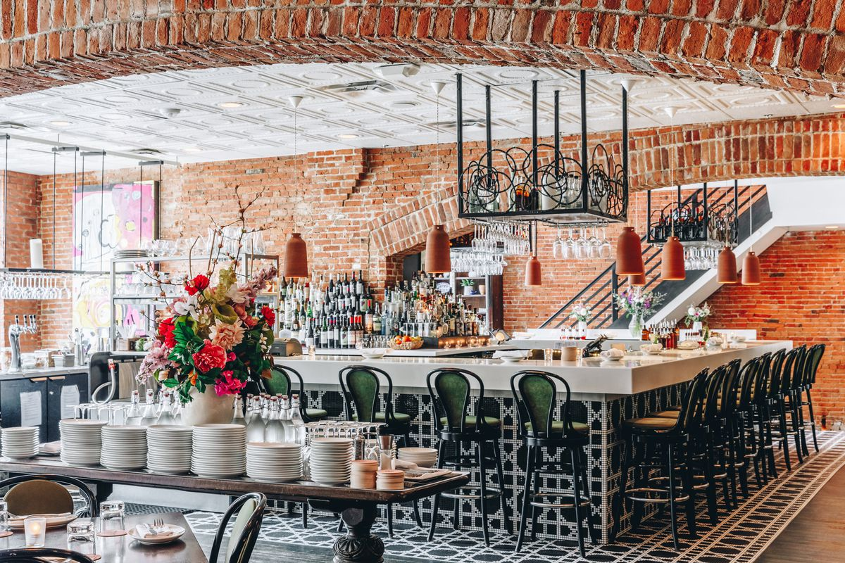 the interior of aventura has brick walls and a rectangular marble bar surrounded by metal stools with green backs.