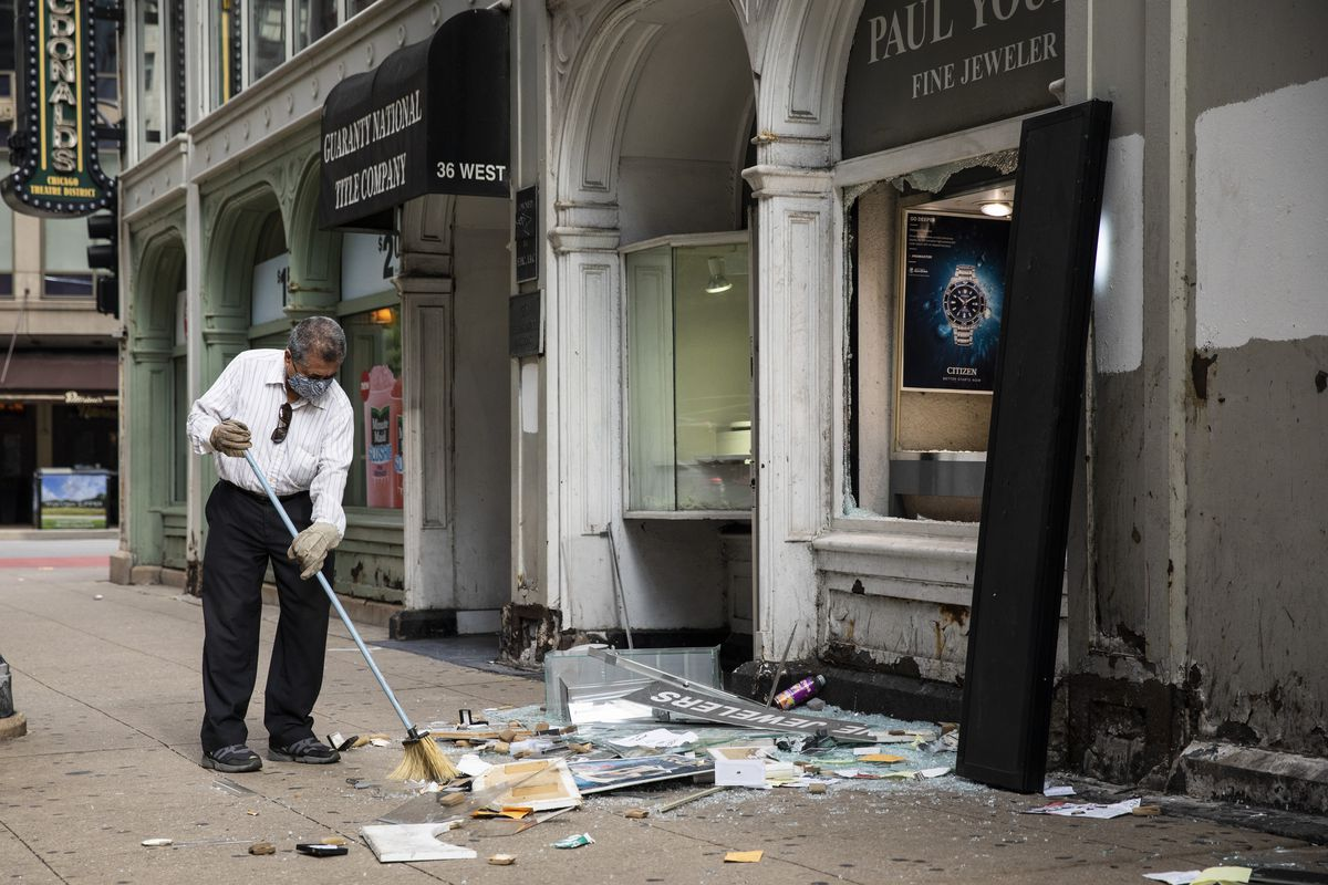 A man sweeps up outside Paul Young Fine Jewelers after looting broke out in the Loop and surrounding neighborhoods overnight, Monday morning.