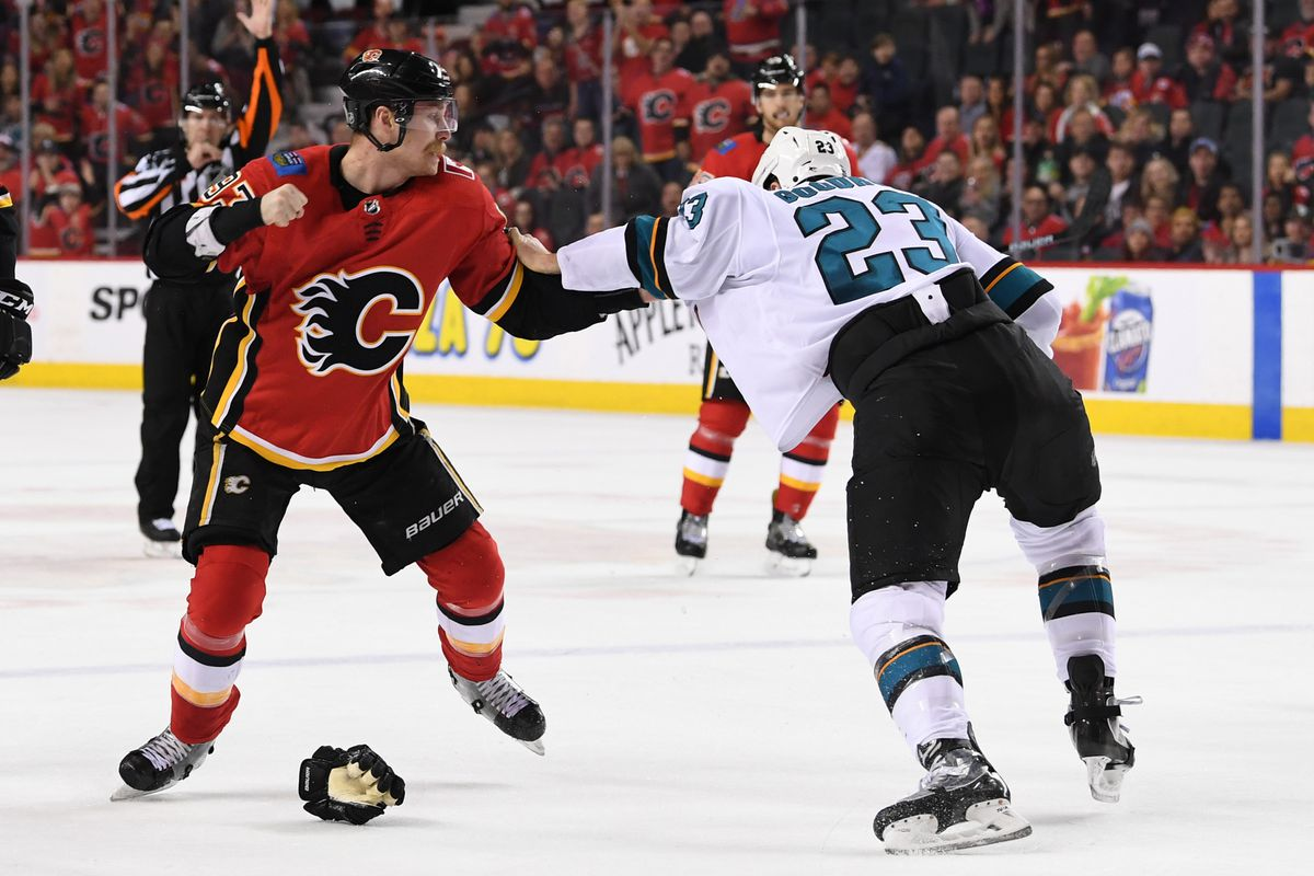 Dec 31, 2018; Calgary, Alberta, CAN; Calgary Flames center Sam Bennett (93) squares off against San Jose Sharks left wing Barclay Goodrow (23) during the third period at Scotiabank Saddledome. The Flames won 8-5.
