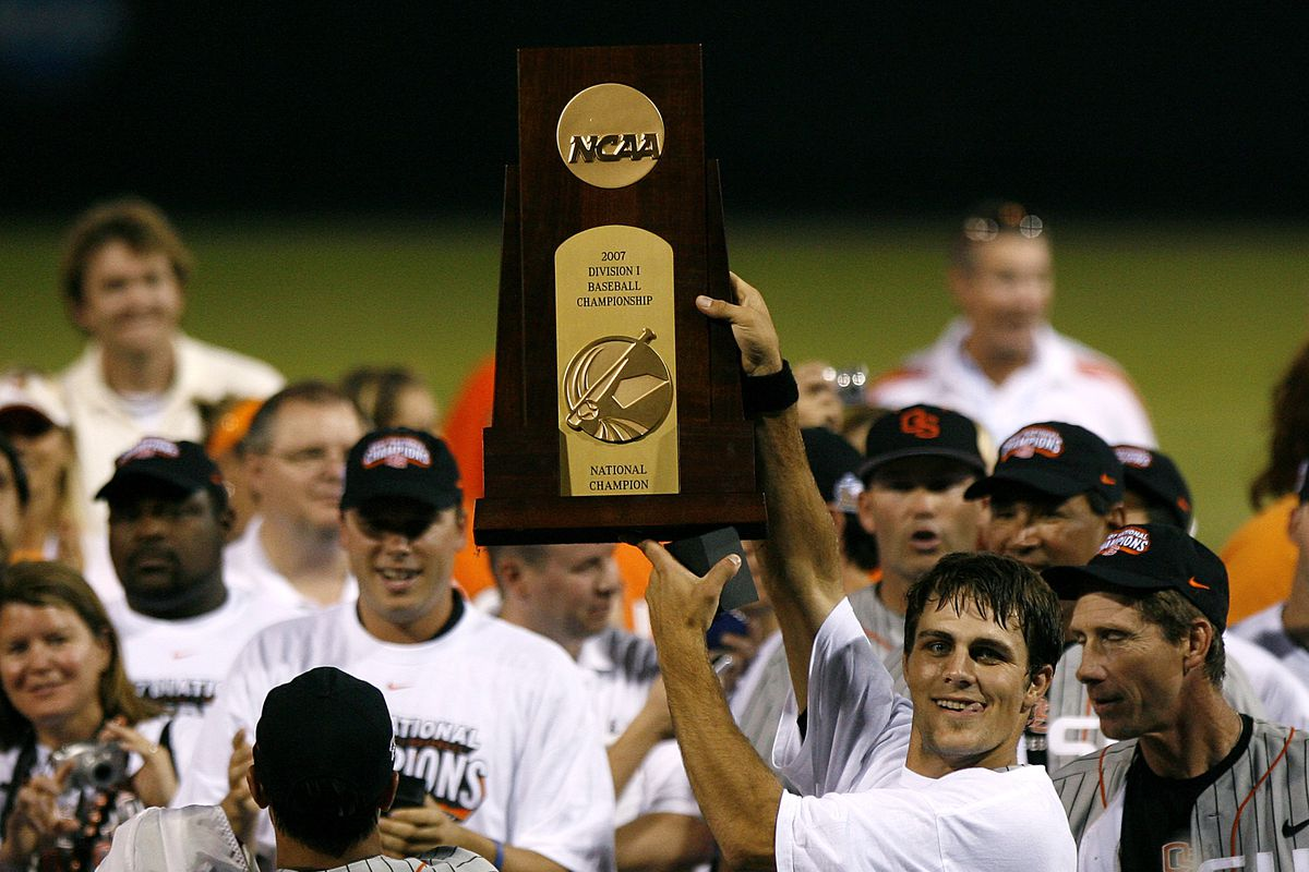 Mitch Canham, new Head Coach for the Beavers, holds up the championship trophy after winning it as a player.