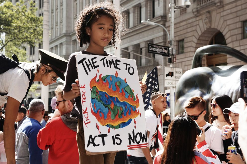 """At the Global Climate Strike in New York City, Yerrhum Lee, age 9, holds a sign that reads, """"The time to act is now"""" around a painting of an Earth on fire."""