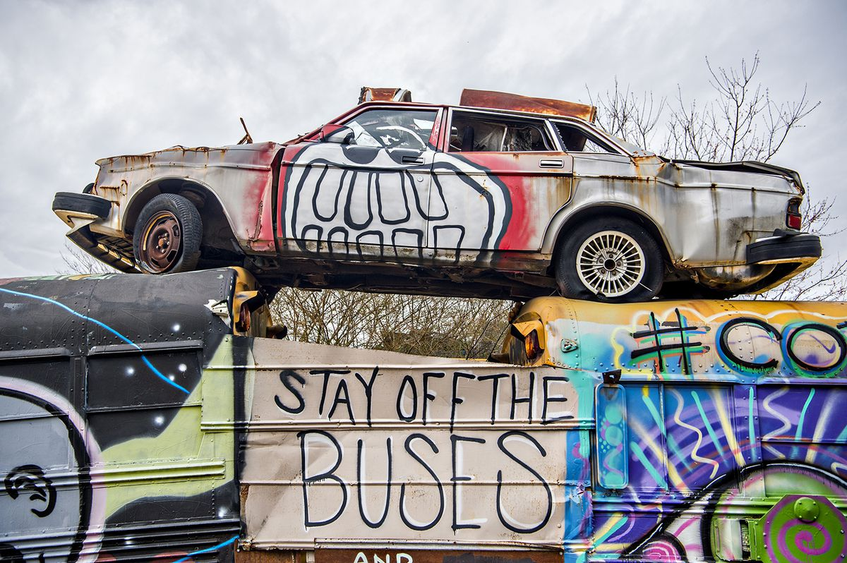 An old junk car stacked on a row of buses.