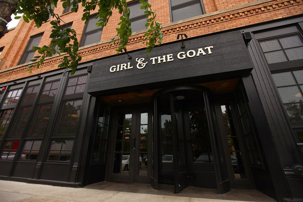 """A large, black entrance to a restaurant with the words """"Girl & the Goat"""" in white lettering above the door."""