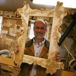 In this April 11, 2012 photo, local woodworking artist Phil Marshall poses with a nearly-completed mirror frame at his studio outside of Fairbanks, Alaska. Marshall is the creator of distinctive, one-of-a-kind wooden furniture.