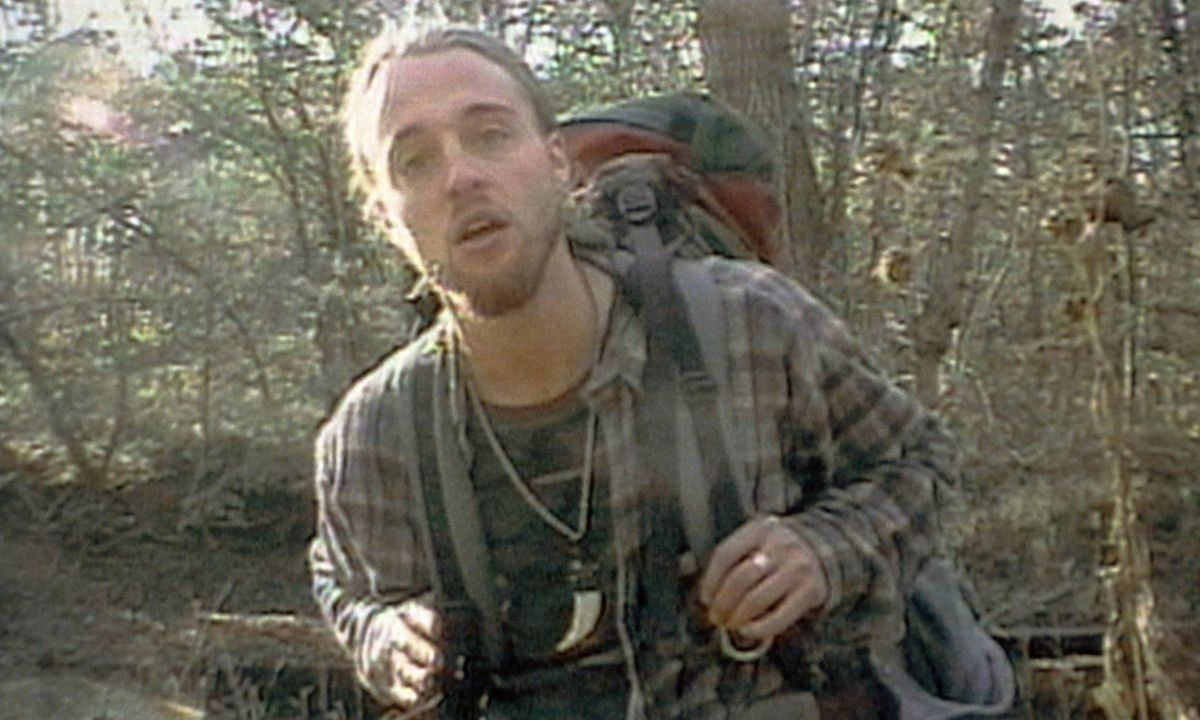 Joshua Leonard, in a grubby flannel and heavy backpack, stands in a forest gaping at the camera in The Blair Witch Project.