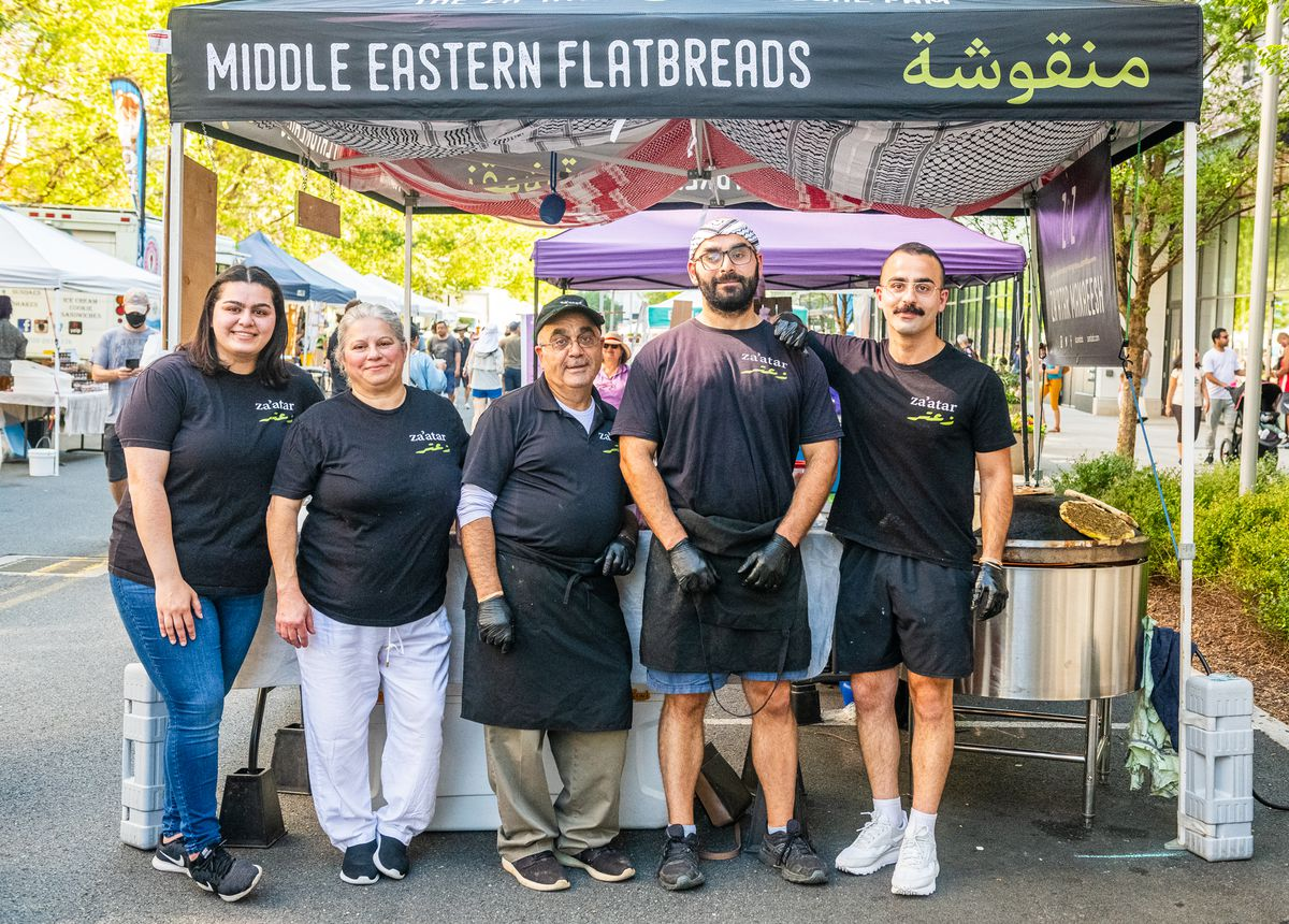 A group shot of the Dubbaneh family in front of their Z&Z za'atar tent at the farmer's market in Fairfax