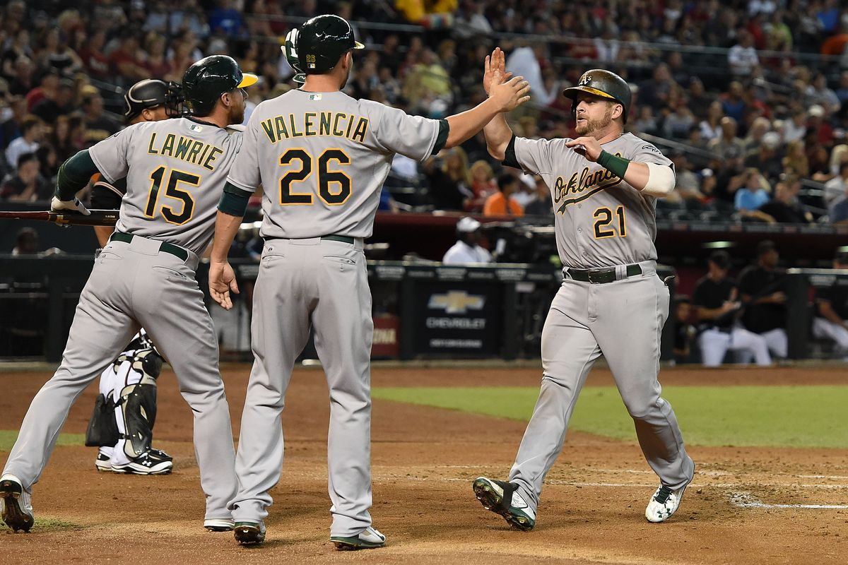 Stephen Vogt celebrates with Danny Valencia and Brett Lawrie after hitting a two-run home run in the second inning against the Arizona Diamondbacks.
