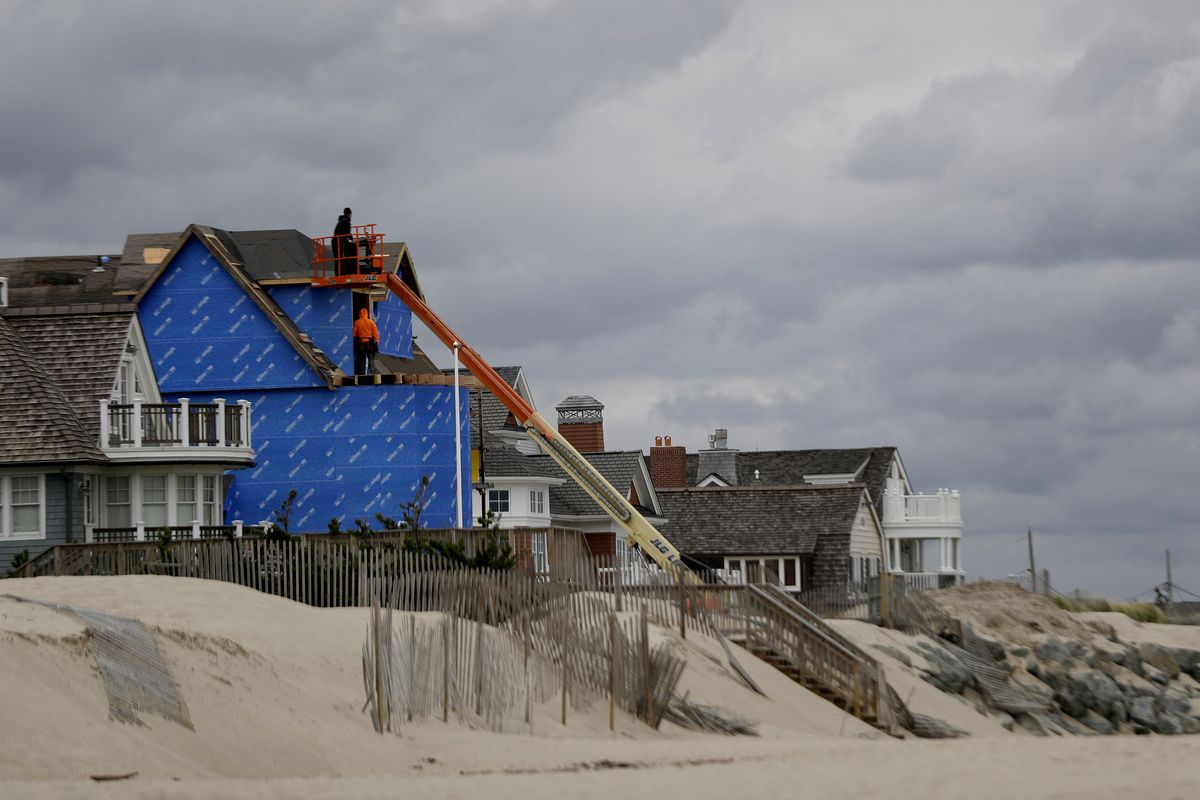 A row of homes on the Atlantic coast, with one under construction after water damage.