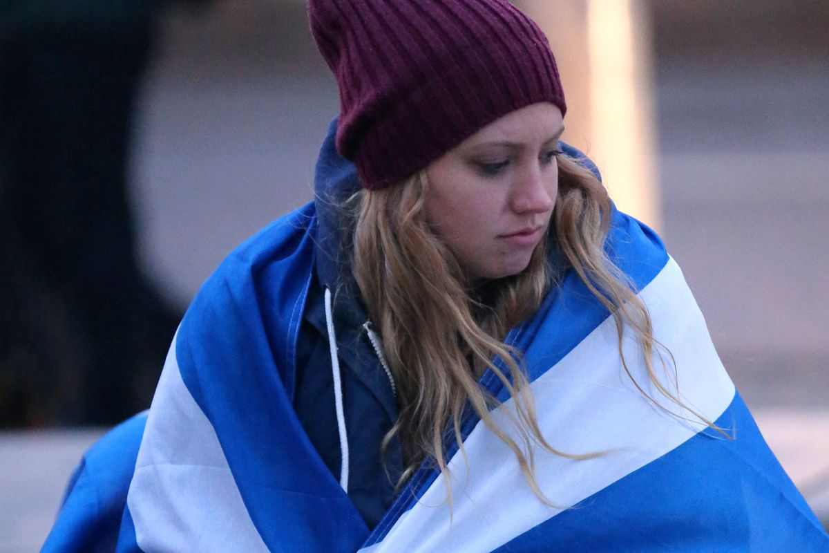 A Yes voter consoles herself, wrapped in the Scottish flag.