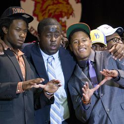 Malcolm Lewis, left, and Tracy Howard, right, Miramar, Fla. high school football players, pose for photos with their coach, Damon Cogdell, center, after the two players announced, Tuesday, Feb. 1, 2012 that they will play college football for the University of Miami.