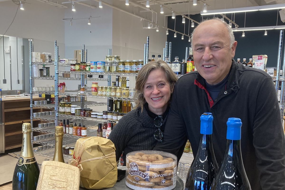 Two people stand behind a selection of cheeses and wines, inside a brightly lit grocery store