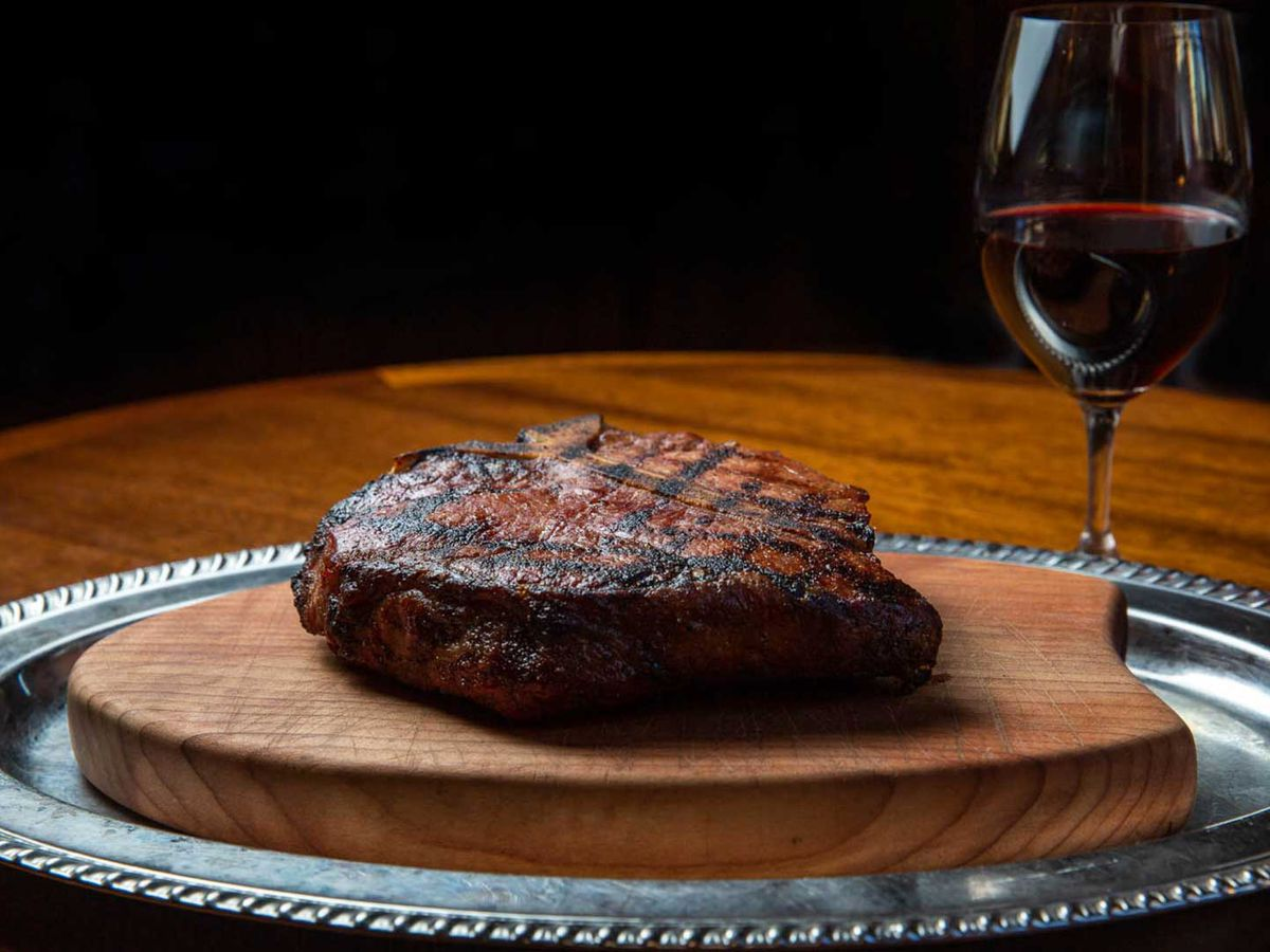 A dry-aged steak on a wooden board, next to a glass of red wine.