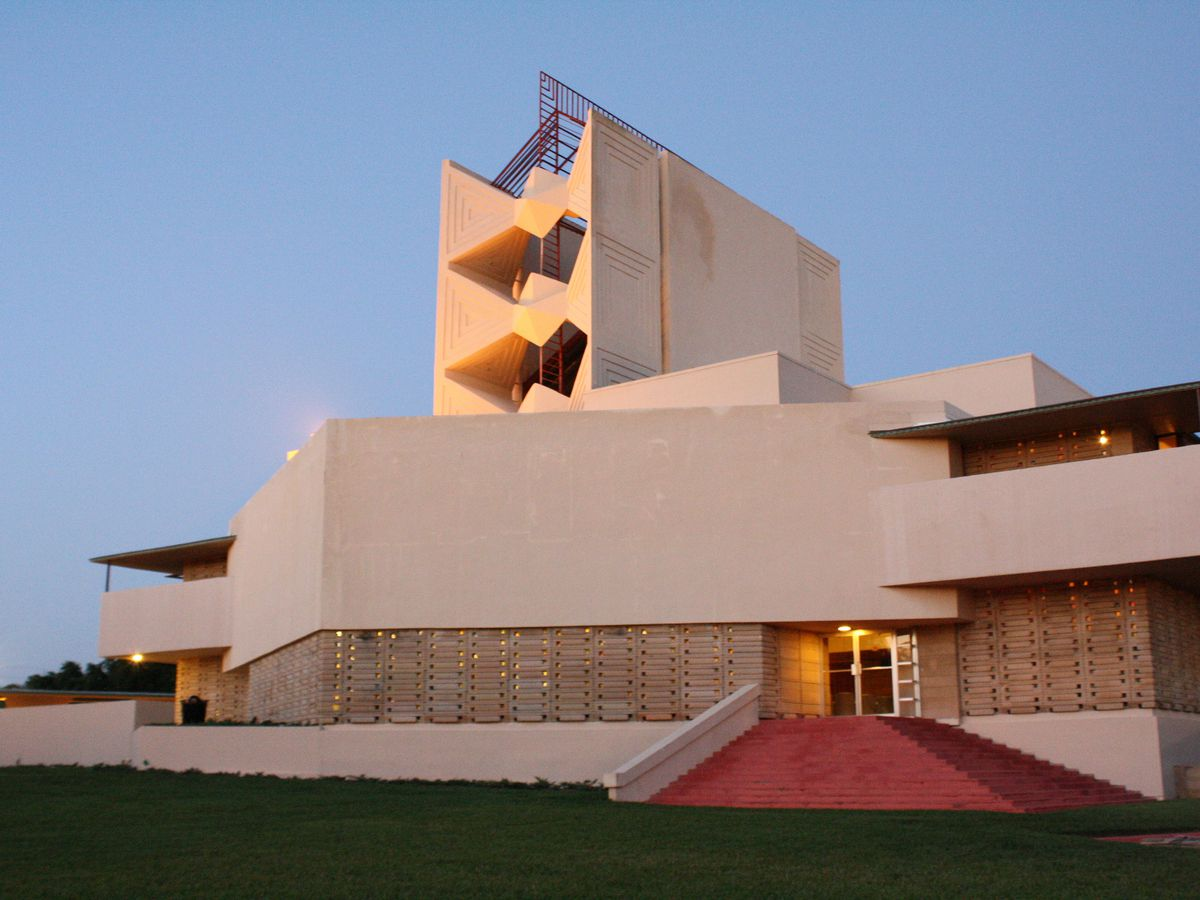 Child of the Sun by Frank Lloyd Wright. The facade is tan and terraced. There is a red staircase.