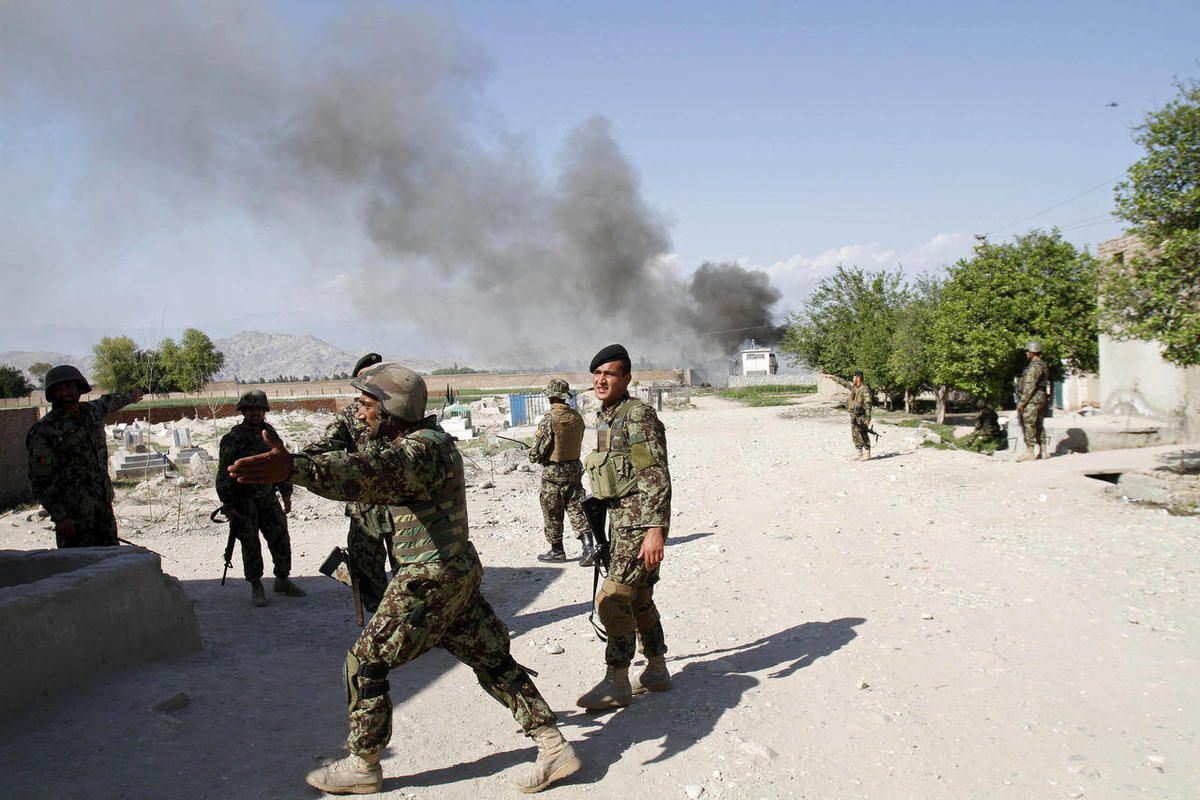 Afghan soldiers react after a suicide attack on the U.S.-led provincial reconstruction team (PRT) compound in the Behsood district of Jalalabad, east of Kabul Afghanistan, on Sunday, April 15, 15 2012. The Taliban launched a series of coordinated attacks