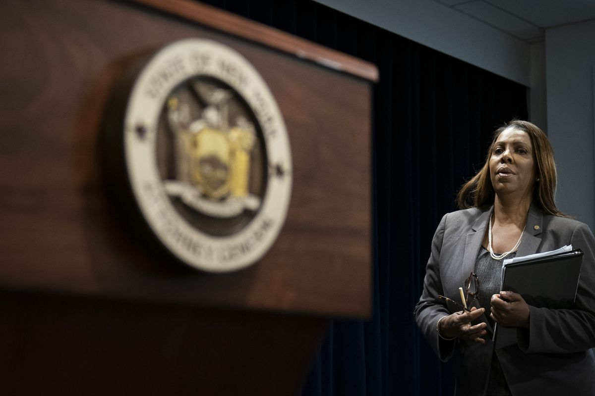 New York Attorney General Letitia James stands next to the state seal while holding a binder.
