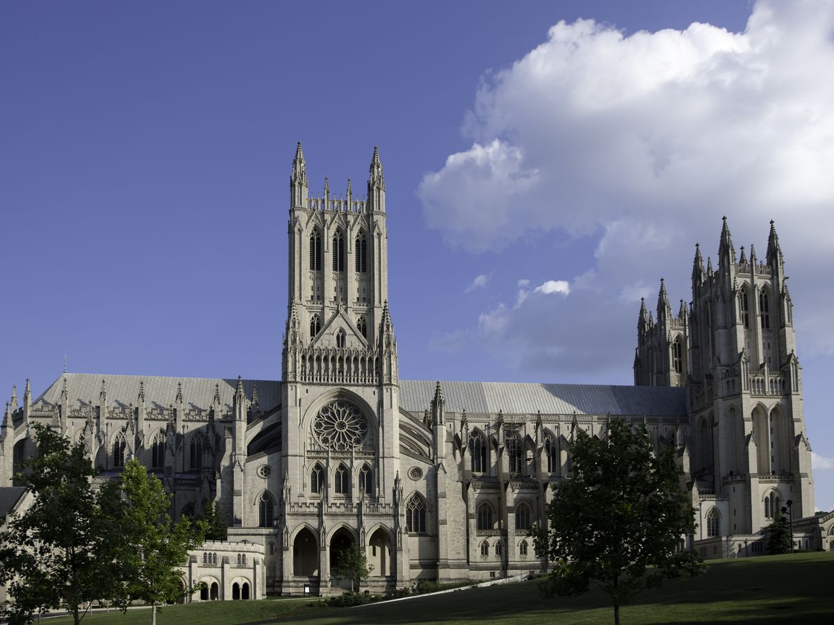 The exterior of the Washington National Cathedral. The facade is tan and there are elaborately designed towers.