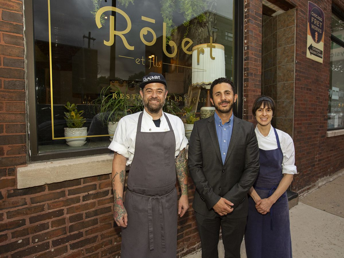 Three folks in front of a restaurant
