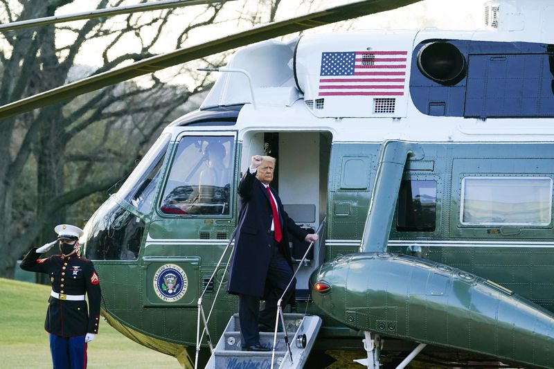 President Donald Trump gestures as he boards Marine One on the South Lawn of the White House, January 20, 2021, in Washington, DC.