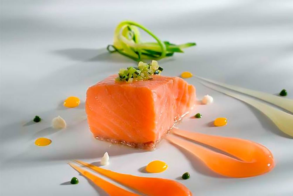 A spare, modernist plating of salmon, with a single cube of fish surrounded by long streaks of sauce on a gray background.