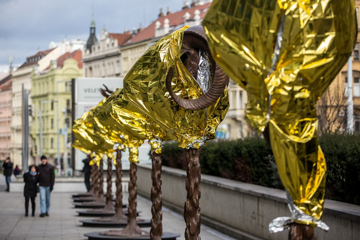 row of golden crumply statues by artist Ai Wei Wei on Prague street with Prague-looking buildings in background