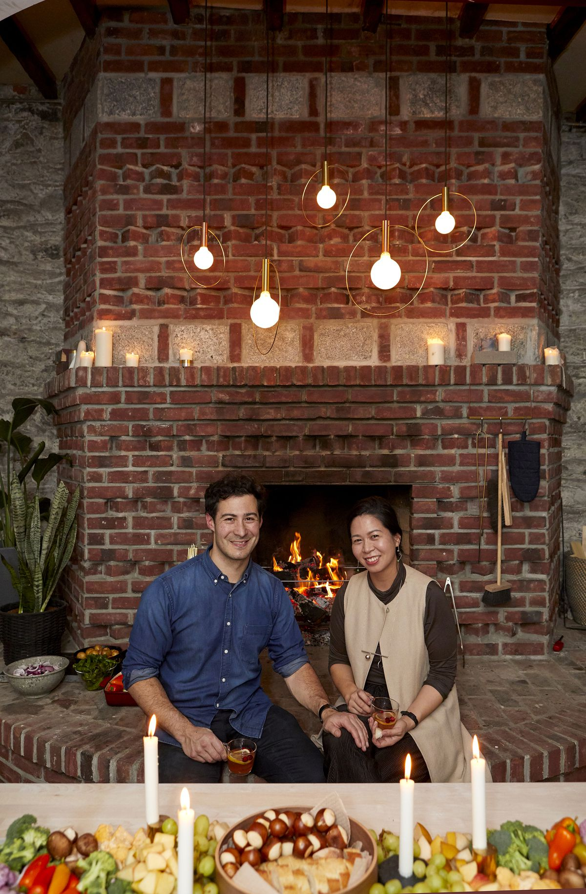 Lee and Davis sitting in front of their lit fireplace.