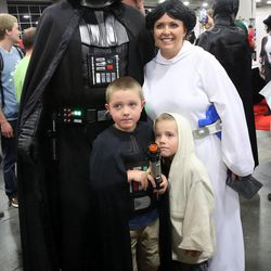 From left, Harper Brace, Collier Brace and Heather Brace pose for a photo with Darth Vader at Comic Con at the Salt Palace Convention Center in Salt Lake City on Saturday, Sept. 7, 2013.