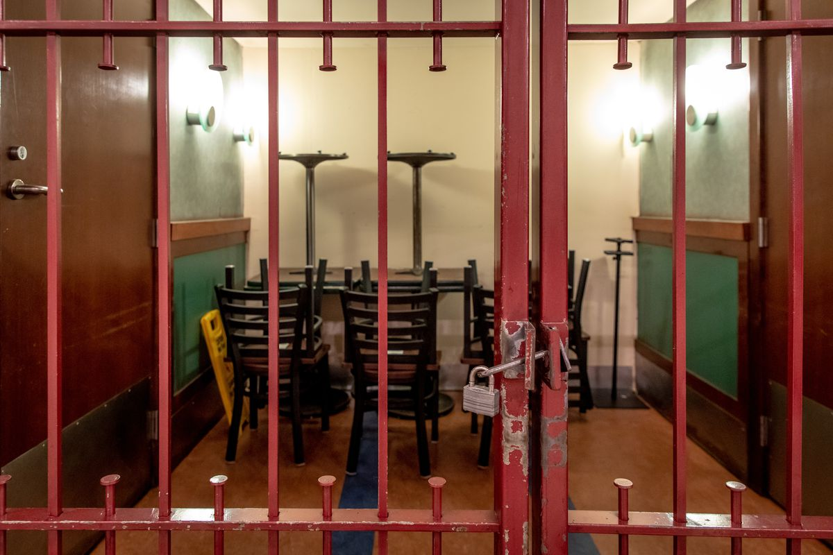 Chairs and tables are locked behind a cage.