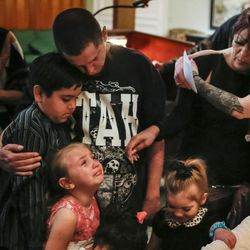 Nate Hall, center, embraces his son, Gabriel, while standing with Alizea Gobel, 5, bottom left, her sister, Haze Hall, 4, bottom right, and other family members in front of Matt Hall's casket during his funeral at Myers Mortuary in Ogden on Saturday, April 15, 2017. Matt Hall was in jail for 15 months until he smashed his head into a wall and jumped off a railing in February. He was paralyzed from the shoulders down until dying from his injuries on April 7.