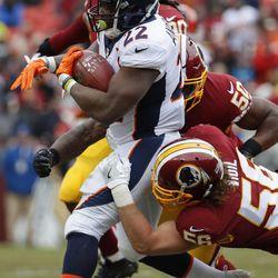 Denver Broncos running back C.J. Anderson (22) is stopped by Washington Redskins linebacker Zach Vigil (56) during the first half an NFL football game in Landover, Md., Sunday, Dec 24, 2017. (AP Photo/Alex Brandon)